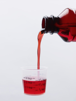 Cough Syrup Pouring into a Measuring Cup.
